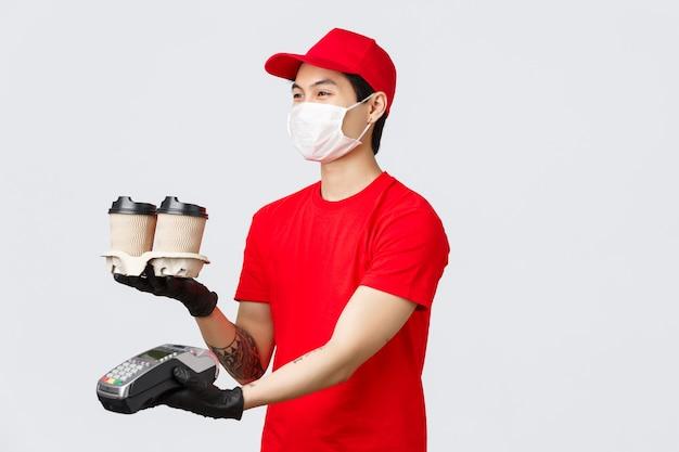 Dostawa zbliżeniowa, bezpieczny zakup i zakupy podczas koncepcji koronawirusa. przyjazny uśmiechnięty kurier w czerwonym mundurze wydający zamówienie klienta z kawą i terminalem pos, klient płaci za dostawę.