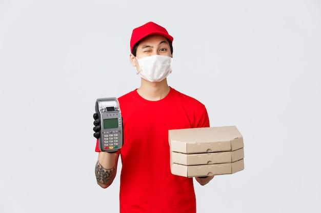 Dostawa zbliżeniowa, bezpieczny zakup i zakupy podczas koncepcji koronawirusa. wesoły pracownik fast-foodu lub kurier w czerwonej czapce mundurowej, koszulce, przynieś terminal pos z pizzą do klienta, przynieś porządek.