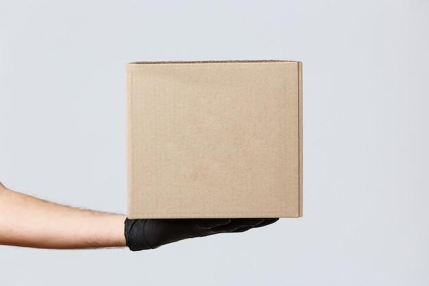 Dostawa zbliżeniowa, koncepcja covid-19 i zakupy. obraz dłoni kuriera w gumowych rękawiczkach trzymających pakiet, pudełko z zamówieniem klienta. dostawca rozdaje paczkę klientowi