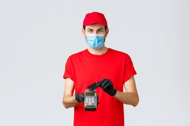 Dostawa zbliżeniowa, płatność i zakupy online podczas covid-19, samodzielna kwarantanna. kurier zapewnia bezpieczne płatności, kupując kartą kredytową przyłożoną do terminala pos, noś maskę na twarz i rękawiczki