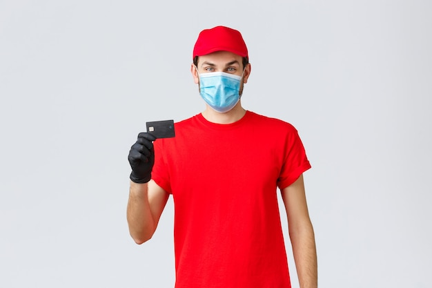 Dostawa zbliżeniowa, płatność i zakupy online podczas covid-19, samodzielna kwarantanna. młody kurier w czerwonej czapce mundurowej, masce na twarz i rękawiczkach, pokazując kartę kredytową, łatwo płacić i zamawiać