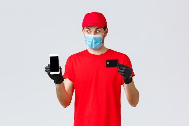 Dostawa zbliżeniowa, płatność i zakupy online podczas covid-19, samodzielna kwarantanna. podekscytowany kurier w czerwonym mundurze, masce na twarz i rękawiczkach, popatrz na wyświetlacz smartfona, pokaż kartę kredytową, opłaci zamówienie.