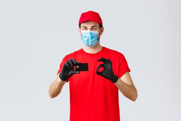 Dostawa zbliżeniowa, płatność i zakupy online podczas covid-19, samodzielna kwarantanna. przyjazny kurier w czerwonym mundurze, czapce i koszulce, załóż maskę i rękawiczki, kciuk w górę zaleca płatność kartą kredytową