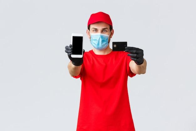 Dostawa zbliżeniowa, płatność i zakupy online podczas covid-19, samodzielna kwarantanna. przyjazny kurier w czerwonym mundurze, masce i rękawiczkach, pokazujący ekran smartfona i kartę kredytową, zamawiający internet.