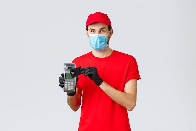 Dostawa zbliżeniowa, płatność i zakupy online podczas covid-19, samodzielna kwarantanna. przyjazny kurier w czerwonym mundurze, rękawiczkach i masce na twarz, pokazujący zamówienie z terminalem pos i kartą kredytową
