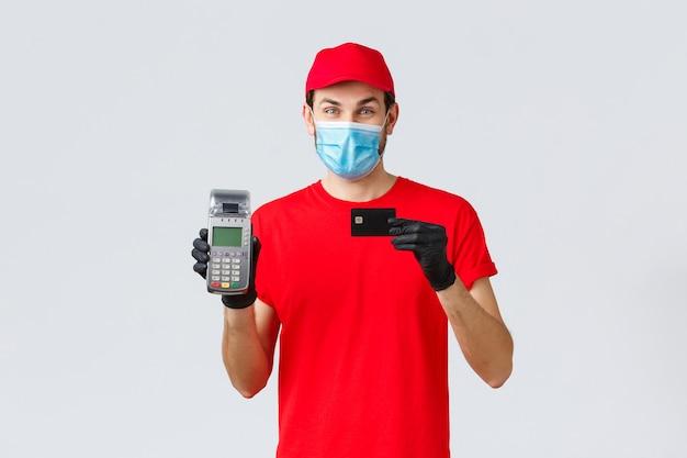 Dostawa zbliżeniowa, płatność i zakupy online podczas covid-19, samodzielna kwarantanna. przystojny kurier z terminalem płatniczym pos i kartą kredytową, zapewnia bezpieczną płatność, nosi maskę na twarz i rękawiczki