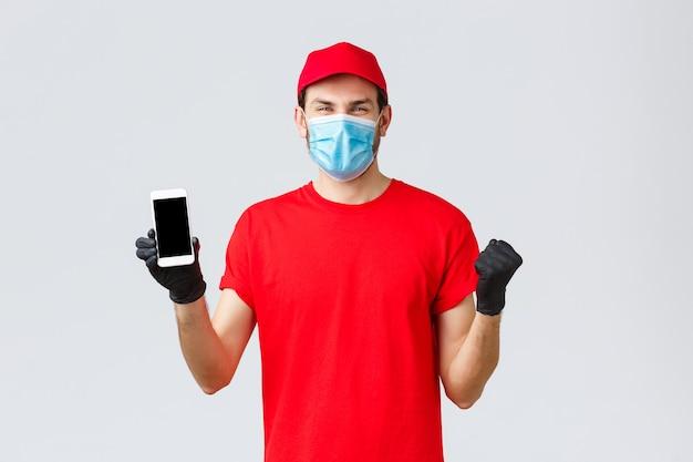 Dostawa zbliżeniowa, płatność i zakupy online podczas covid-19, samodzielna kwarantanna. radosny, wesoły kurier w czerwonej mundurowej czapce, koszulce świętującej niesamowitą promocję, pokaż ekran smartfona, załóż maskę