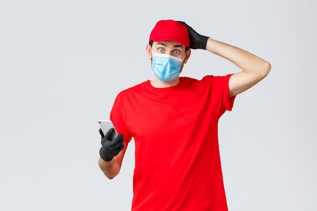 Dostawa zbliżeniowa, płatność i zakupy online podczas covid-19, samodzielna kwarantanna. zdezorientowany i niezdecydowany kurier nie wie, noś maskę na twarz i rękawiczki, drap głowę, trzymaj smartfona