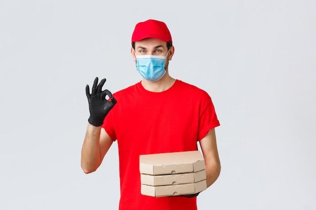 Dostawa żywności, aplikacja, sklep spożywczy online, zakupy zbliżeniowe i koncepcja covid-19. kurier gwarantuje jakość pizzy, trzymanie pudełek, poprawny znak w rekomendacji lub aprobacie, noszenie maski