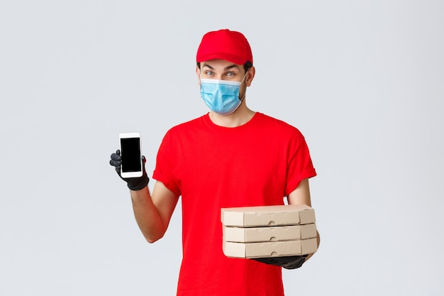 Dostawa żywności, aplikacja, sklep spożywczy online, zakupy zbliżeniowe i koncepcja covid-19. kurier promuje specjalne rabaty lub aplikację na dostawę do domu, trzymanie pizzy i telefonu