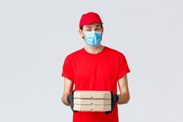Dostawa żywności, aplikacja, sklep spożywczy online, zakupy zbliżeniowe i koncepcja covid-19. przyjemny kurier w czerwonym mundurze przyniesie pizzę w pudełkach, założy maskę na twarz i gumowe rękawiczki, wyda polecenie clint