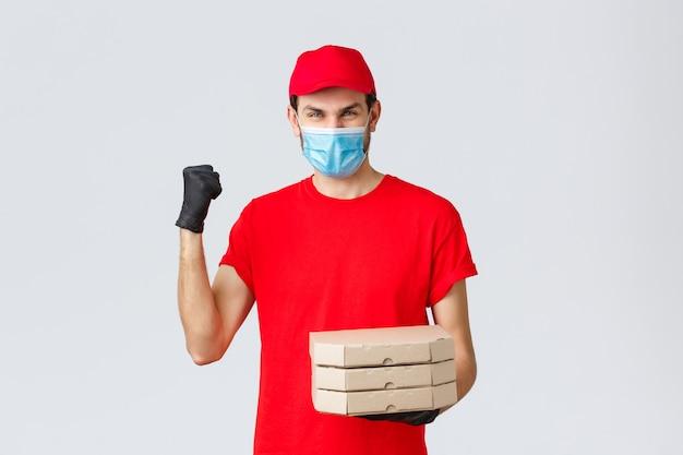Dostawa żywności, aplikacja, sklep spożywczy online, zakupy zbliżeniowe i koncepcja covid-19. szybka i bezpieczna dostawa, mistrzowie w branży. kurier w czerwonej jednolitej pompie pięściowej, dostarcza zamówienie na pizzę
