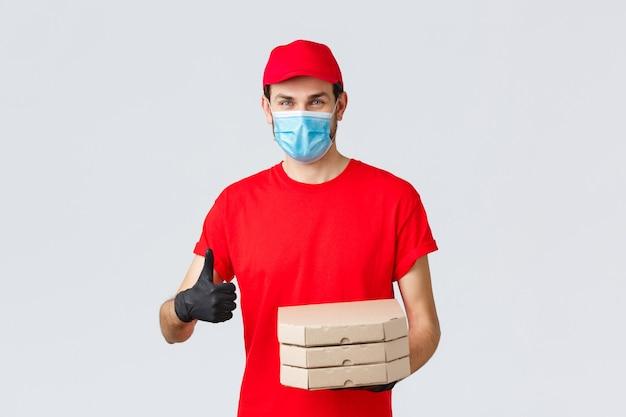 Dostawa żywności, aplikacja, sklep spożywczy online, zakupy zbliżeniowe i koncepcja covid-19. uśmiechnięty kurier kaukaski w czerwonym mundurze, rękawiczkach i masce na twarz, zapewnia najlepsze oferty, ekspresową dostawę pizzy
