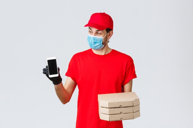 Dostawa żywności, aplikacja, sklep spożywczy online, zakupy zbliżeniowe i koncepcja covid-19. zaskoczony uśmiechnięty kurier w czerwonym mundurze, trzymający pudełka z pizzą i smartfonem, pokazujący aplikację do premii lub dostawy