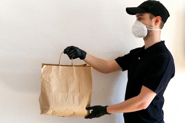 Dostawa żywności i towarów podczas pandemii koronawirusa. doręczyciel w mundurze. doręczyciel trzyma worek papieru rzemieślniczego. człowiek w ochronne maski medyczne i gumowe rękawice.