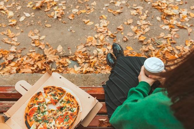 Dostawa żywności. kobieta siedzi na ławce parku publicznego. kopiuj przestrzeń