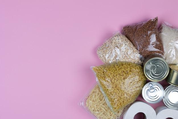 Dostawa żywności, kryzys darowizny zaopatrzenie w żywność na okres izolacji kwarantanny koronawirus, ryż, makaron, płatki owsiane, żywność w puszkach, papier toaletowy, gryka na różowym tle