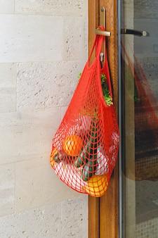 Dostawa żywności lub darowizna w siatkowej torbie na klamce drzwi podczas kwarantanny