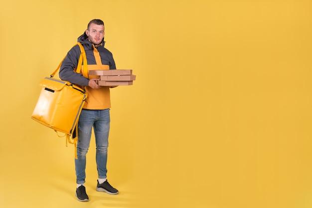 Dostawa żywności młody człowiek w żółtej kurtce