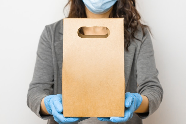 Dostawa żywności podczas kwarantanny z powodu wybuchu koronawirusa. kobieta trzyma pudełko w medycznych rękawiczkach i masce ochronnej.