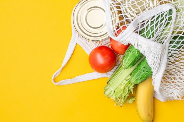 Dostawa żywności. produkty spożywcze w torbie strunowej na żółtym tle.