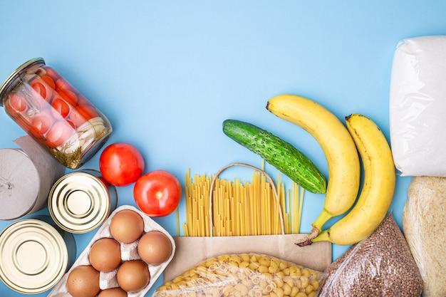 Dostawa żywności. ryż, kasza gryczana, makaron, konserwy, cukier, pomidory, ogórki, banany na niebieskim tle.