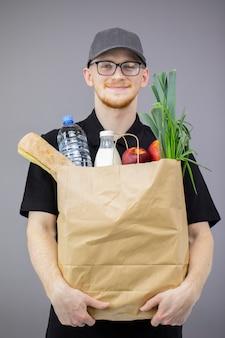 Dostawa żywności usługi człowiek z pudełko spożywcze na szarej ścianie na białym tle
