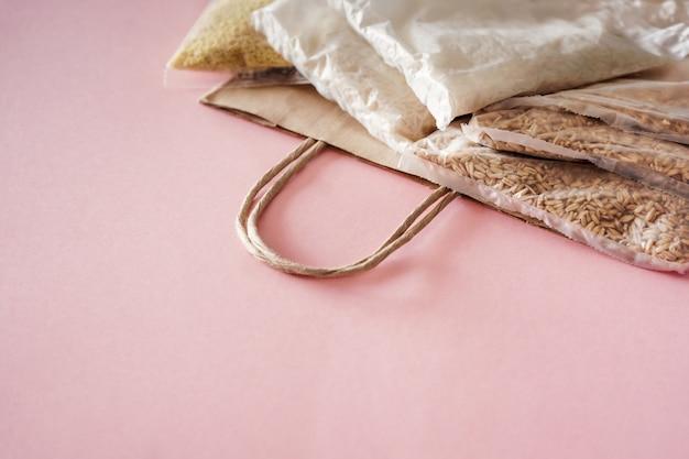 Dostawa żywności w okresie koronawirusa. torba papierowa z zapasem jednostek na okres izolacji kwarantanny, układ na różowej ścianie. ryż, proso, płatki owsiane w przezroczystej torbie.