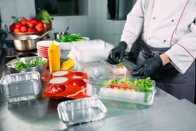 Dostawa żywności w restauracji. szef kuchni przygotowuje jedzenie w restauracji i pakuje je w naczynia jednorazowe.