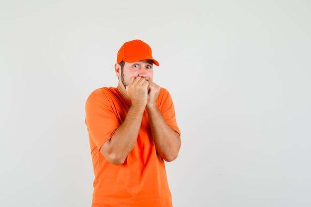Dostawca gryzie pięści emocjonalnie w pomarańczowy t-shirt, czapkę i wyglądający na przestraszony, widok z przodu.