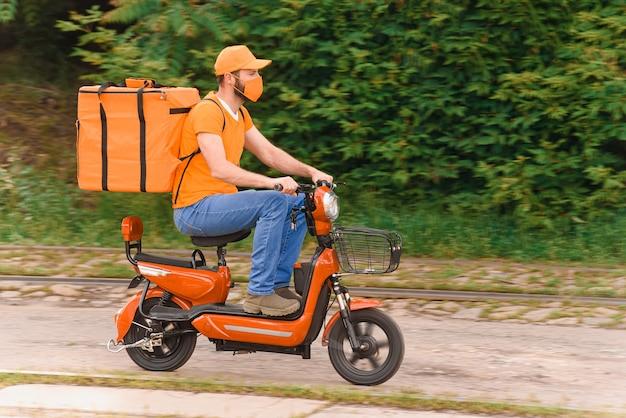 Dostawca jedzenia w kolorze pomarańczowym z ochronną maską medyczną na twarzy jedzie na motorowerze