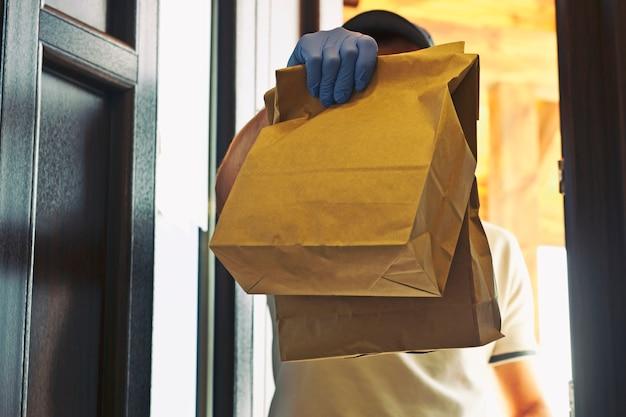 Dostawca jedzenia w rękawiczkach i masce na twarz wydaje klientowi zamówienie w domu