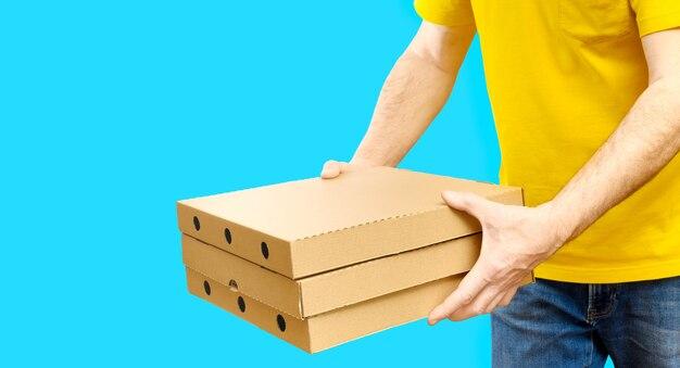 Dostawca niesie pudła pizzy z usługą dostawy fast foodów na kopię