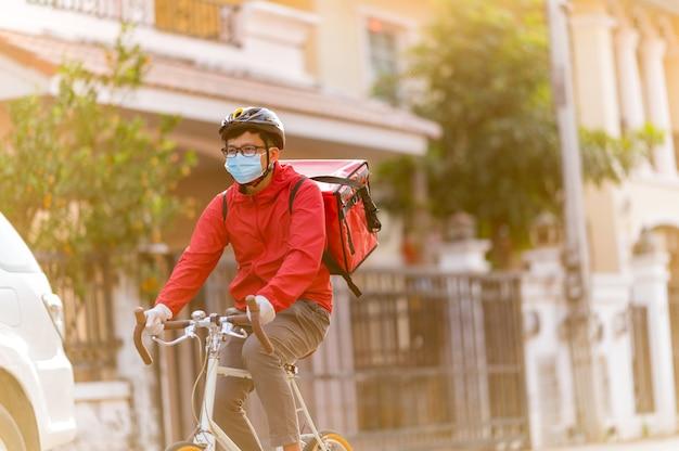 Dostawca noszący maskę ochronną na twarz, aby uniknąć wirusa koronowego czerwony mundur kolarstwo w celu dostarczania produktów klientom w domu.