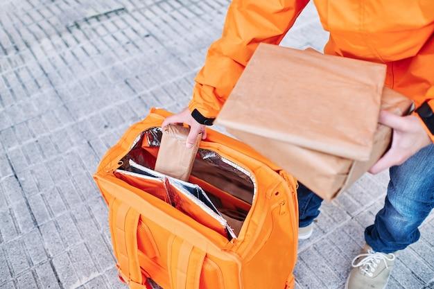 Dostawca odbierający paczki z plecaka dostawczego na chodniku