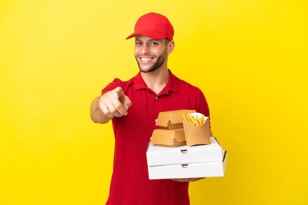 Dostawca pizzy, który odbiera pudełka po pizzy i hamburgery na białym tle, wskazując przód ze szczęśliwym wyrazem twarzy