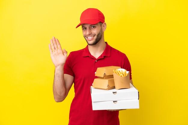 Dostawca pizzy, który podnosi pudełka po pizzy i hamburgery na białym tle, pozdrawiając ręką ze szczęśliwym wyrazem twarzy