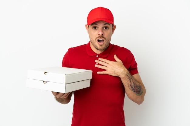 Dostawca pizzy w mundurze roboczym, który podnosi pudełka po pizzy nad odosobnioną białą ścianą, zaskoczony i zszokowany, patrząc w prawo
