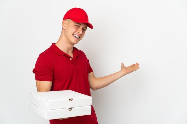Dostawca pizzy w mundurze roboczym, zbierając pudełka po pizzy na białej ścianie, wyciągając ręce na bok, by zaprosić do przyjścia
