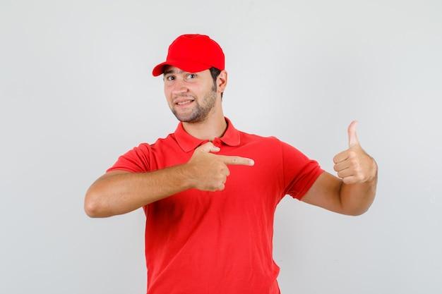 Dostawca w czerwonej koszulce, czapka z daszkiem, wskazując na kciuk i patrząc wesoło