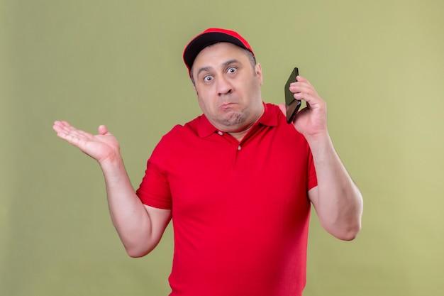 Dostawca w czerwonym mundurze i czapce stoi ze smartfonem, wzruszając ramionami i rozkładając ręce, nie rozumiejąc, co się stało, nieświadomy i zdezorientowany wyraz twarzy stojącej nad gr