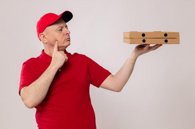 Dostawca w czerwonym mundurze i czapce, trzymający pudełka po pizzy, patrzący na nie z zamyśloną miną i zaintrygowany