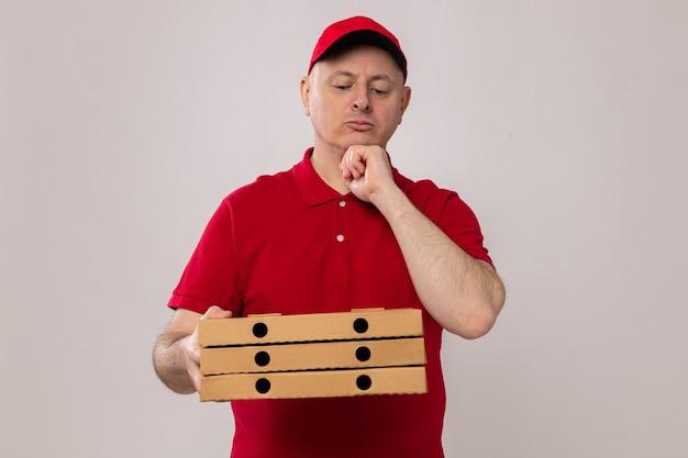 Dostawca w czerwonym mundurze i czapce, trzymający pudełka po pizzy, patrzący na nie z zamyślonym wyrazem twarzy, myślący stojąc na białym tle