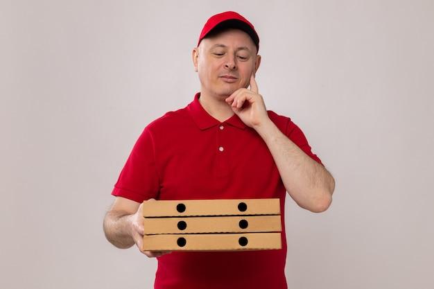 Dostawca w czerwonym mundurze i czapce, trzymający pudełka po pizzy, patrzący na nie z zamyślonym wyrazem twarzy, uśmiechający się, myślący pozytywnie