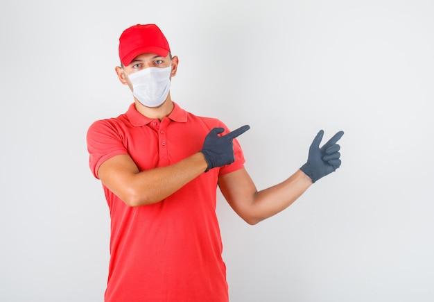 Dostawca w czerwonym mundurze, masce medycznej, rękawiczkach wskazujących palcami i wyglądającego na pewnego siebie