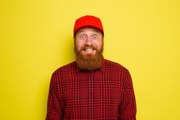 Dostawca w kapeluszu i brodzie ma radosny wyraz twarzy