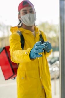 Dostawca w masce i rękawiczkach lateksowych, ubrany w torbę termiczną za plecami i sięgający ręką do otwarcia drzwi
