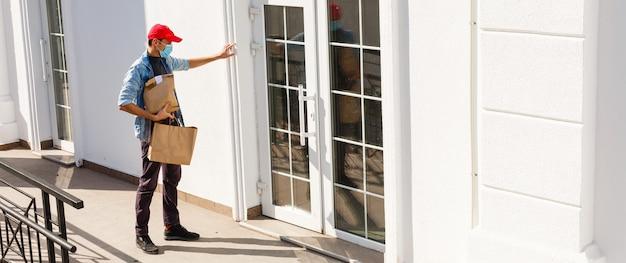 Dostawca w masce ochronnej w pobliżu domu klienta, na zewnątrz
