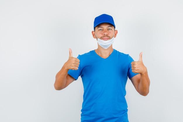 Dostawca w niebieskiej koszulce, czapce, masce pokazującej kciuki do góry i pozytywnie wyglądającej