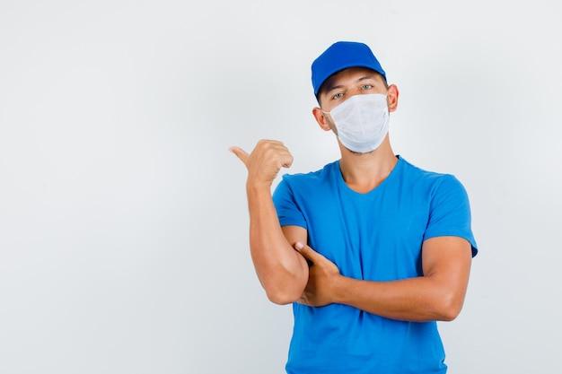 Dostawca w niebieskiej koszulce, czapce, masce wskazującej kciukiem w bok i wyglądającego na pewnego siebie